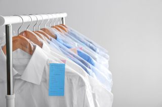 shirts from dry cleaners hanging on garment rack